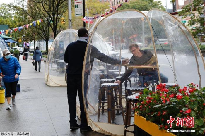 """当地时间10月13日,纽约曼哈顿一家法式餐厅在户外布置""""泡泡屋""""以供顾客用餐,同时达到阻断病毒传播和避风保暖效果。 <a target='_blank' href='http://www.chifinland.cn/'>中新社</a>记者 廖攀 摄"""
