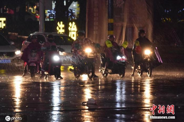 资料图:2020年10月13日,海南省琼海市民在风雨中出行。图片来历:IC photo