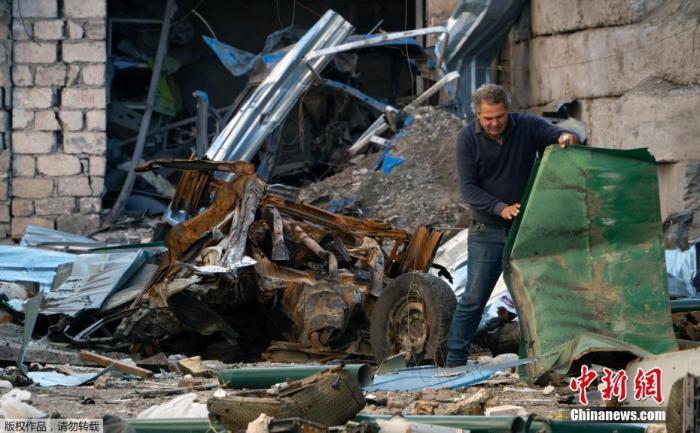 当地时间10月13日,纳卡地区斯捷潘纳克特,一名男子在整理院子里的碎片。