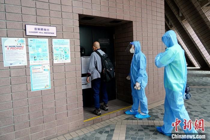 10月14日上午,身穿防护衣的人员进入香港文化中心音乐厅后台进行消毒。香港卫生署卫生防护中心当天公布一宗新冠肺炎初步确诊个案,该宗个案涉及一名35岁男病人,为香港管弦乐团的管乐乐师。病人曾于10月9日及10日晚上在香港文化中心音乐厅参与乐团演出。卫生防护中心建议全面清洁及消毒场地,并暂停开放香港文化中心音乐厅14日。卫生防护中心会向香港文化中心的职员及香港管弦乐团的其他职员派发样本瓶。 中新社记者 张炜 摄