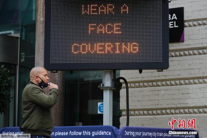 图为伦敦市中心查林十字街车站外,一块显示牌提醒人们佩戴口罩。