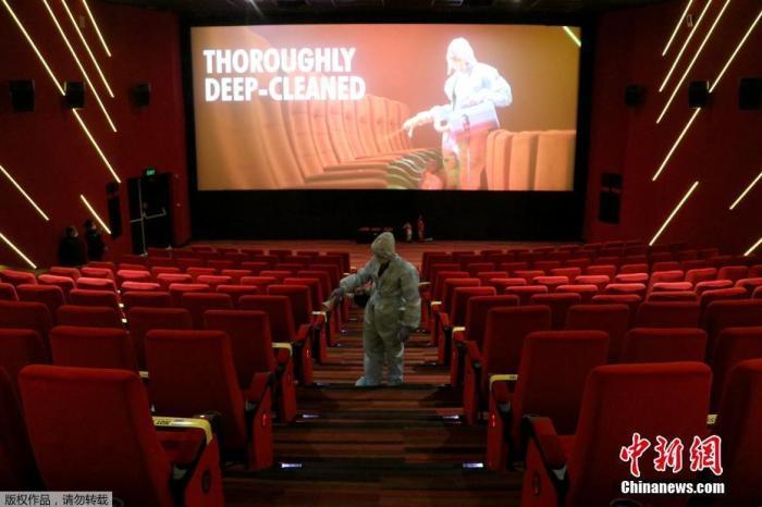当地时间10月13日,印度孟买,一名穿着个人防护设备的工人在Inox Leisure电影院重新开放前为座椅消毒。