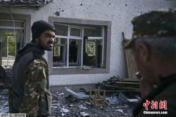 当地时间10月15日,亚美尼亚和阿塞拜疆的冲突在纳卡地区持续进行,Martakert地区一家医院在战火中被摧毁。图为亚美尼亚士兵站在被部分摧毁的军事医院建筑前。