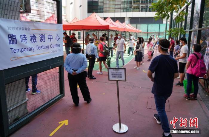 10月18日,众多香港市民在油尖旺临时检测中心门口排起长龙,准备参加新冠病毒检测。当天是最后一个临时检测中心——油尖旺临时检测中心运作的最后一天,众多市民抓紧最后时间前来检测。香港特区政府针对出现社区疫情暴发的地点,上周在湾仔、葵青、九龙城及油尖旺四区各设立一所临时检测中心,方便市民主动进行检测。截至17日晚,四个临时社区检测中心累计收集了超过15,500个样本作检测。 中新社记者 张炜 摄