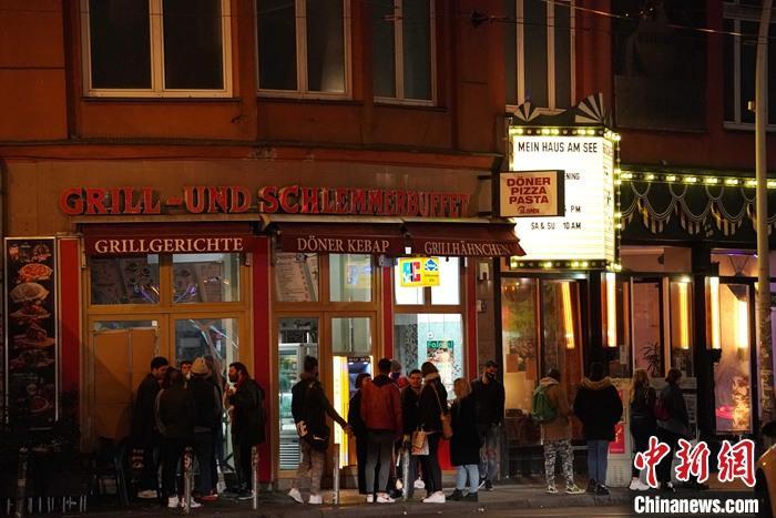 图为10月17日午夜,柏林罗森塔尔广场排队购买宵夜的年轻人。 中新社记者 彭大伟 摄