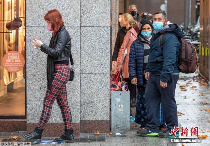 图为爱尔兰都柏林,人们在一家服装店前排队等候是,保持着社交距离。