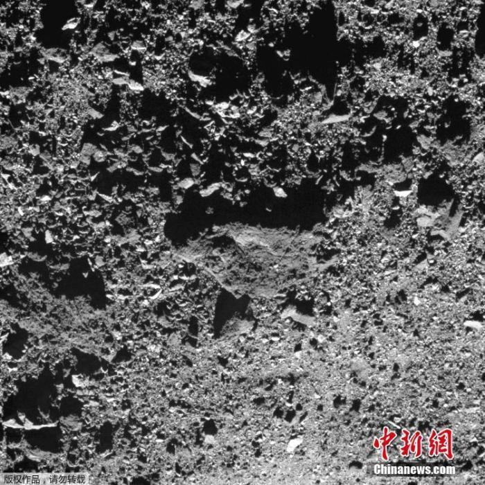 """资料图为OSIRIS-REx探测器拍摄的小行星""""本努""""地面。"""