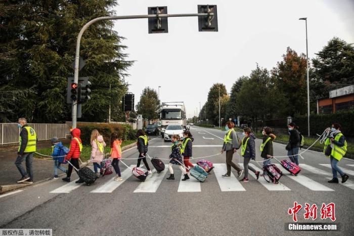 当地时间10月20日,在意大利北部贝卢斯科,孩子们拿着绳子保持社交距离,在志愿者的护送下走向学校。据意大利卫生部门最新发布的新冠患者住院统计资料显示,全国已有17个大区患者住院人数超过了封锁期间的数量。