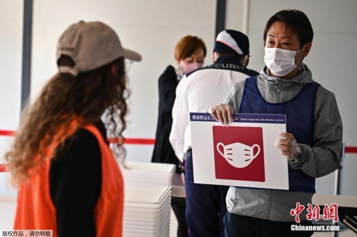当地时间2020年10月21日,东京奥运会和残奥会组织委员会21日在东京向媒体公开了,观众等进入赛场时通过的行李安检区运营的实证试验。奥组委将根据本次的测试结果等,讨论奥运时的对策。图为志愿者提示被检测者注意佩戴口罩。