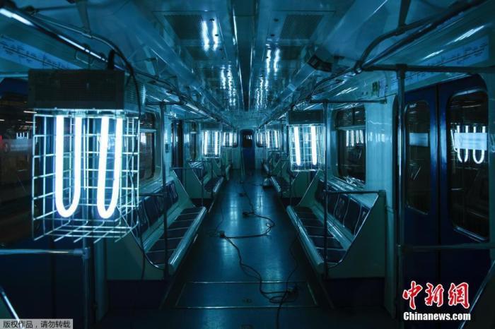当地时间10月22日,俄罗斯莫斯科一列地铁中,工作人员悬挂紫外线灯为地铁车厢消毒。