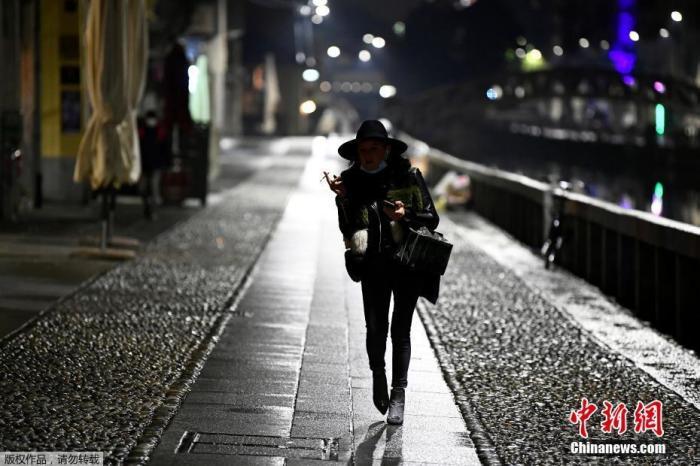当地时间10月22日,意大利米兰,一名女士走在空旷的街头上。