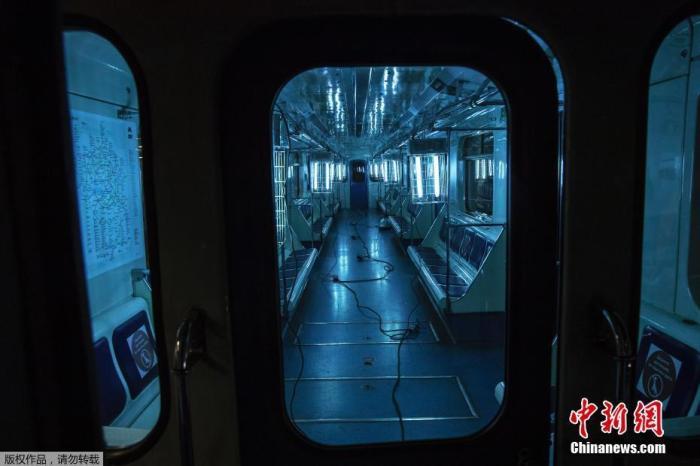 當地時間10月22日,俄羅斯莫斯科一列地鐵中,工作人員懸掛紫外線燈為地鐵車廂消毒。