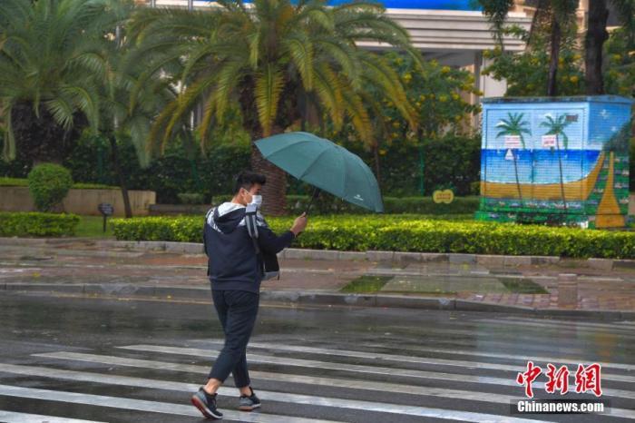 资料图:一行人冒雨出行。中新社记者 骆云飞 摄