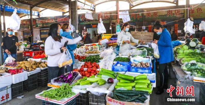 资料图:居民正在买蔬菜。 后彦红 摄