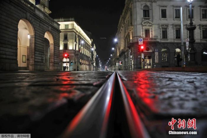 當地時間10月25日凌晨,意大利北部米蘭,斯卡拉歌劇院前的一條空街被紅燈照亮。