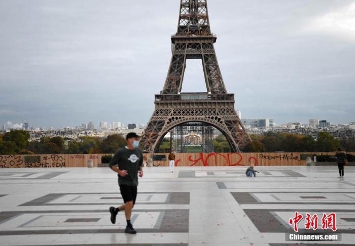 """当地时间10月30日,法国进入第二次全国""""封城"""",以应对新冠肺炎疫情恶化。民众的非必要出行被禁止,非必需公共场所关闭。图为当天巴黎埃菲尔铁塔附近,一名体育锻炼者在跑步。官方准许人们进行适当的体育锻炼,有时间和地点限制。 中新社记者 李洋 摄"""