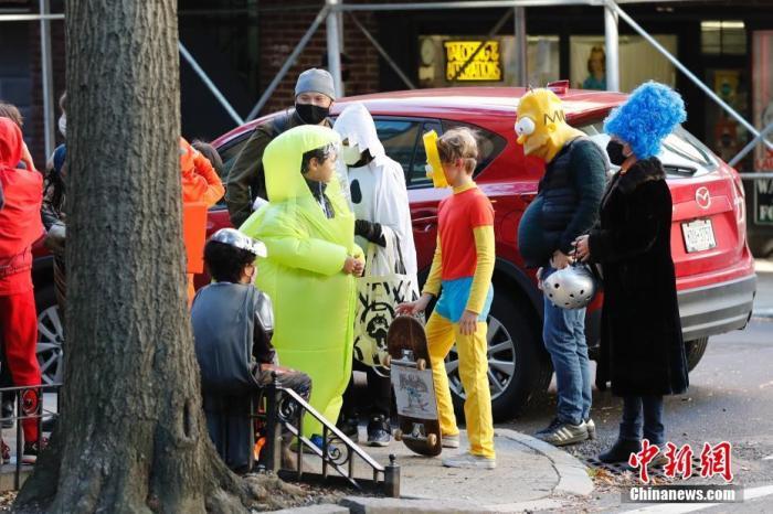 当地时间10月31日,美国传统节日万圣节前夜,纽约市布鲁克林区穿着万圣节装束的孩童到各处要糖,其中一名孩童穿着卡通隔离服。中新社记者 廖攀 摄