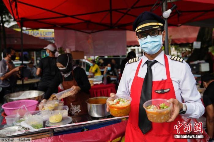 当地时间2020年11月4日,马来西亚雪兰莪州, Azrin Mohamad Zawawi曾是马印航空的一名飞行员,他在10月与其他2200名马印航空的员工被裁员后失业,目前经营着一个食品摊位,出售当地美食,同时也在等待航空业复苏。