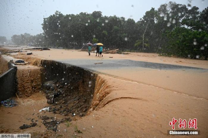 """当地时间11月4日,洪都拉斯持续遭遇飓风""""伊塔"""",给当地带来暴雨。图为人们沿着一条洪水泛滥的路行走。"""