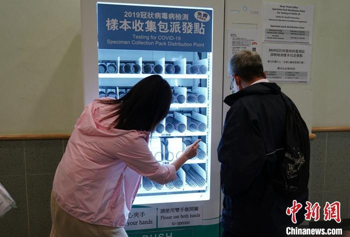 """资料图:有市民在香港西湾河普通科门诊诊所的检测样本收集包""""自动派发机""""上自助领取样本包。 中新社记者 张炜 摄"""