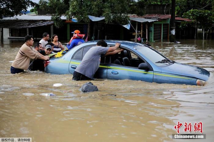"""当地时间11月5日,洪都拉斯拉利马,受飓风""""埃塔""""影响,当地街道被洪水淹没,民众将泡在水中的汽车推出。"""