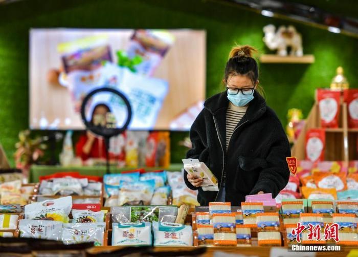 """资料图:2020年""""双11""""期间,新疆一企业展厅内工作人员整理在销的各类农产品。 <a target='_blank'  data-cke-saved-href='http://www.chinanews.com/' href='http://www.chinanews.com/'>中新社</a>记者 刘新 摄"""