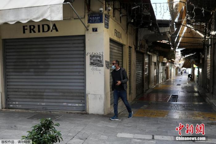资料图:2020年11月7日,希腊雅典,行人经过关闭的商业街。