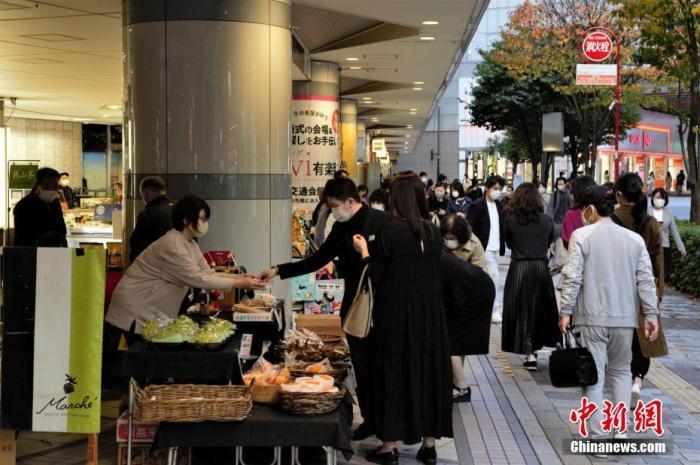 当地时间11月8日,日本经济再生大臣西村康稔表示,希望对疫情继续保持警惕,加快制定冬季防疫对策。近期日本疫情有反弹趋势。图为东京民众在水果摊购物。 中新社记者 吕少威 摄