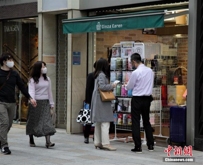 图为东京民众在商店购买口罩。中新社记者 吕少威 摄