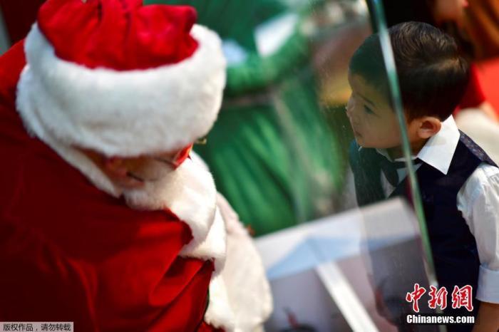 资料图:当地时间11月14日,美国宾州一家购物中心内,圣诞老人的面前竖起了一块树脂玻璃,小朋友隔着玻璃与圣诞老人互动合影。