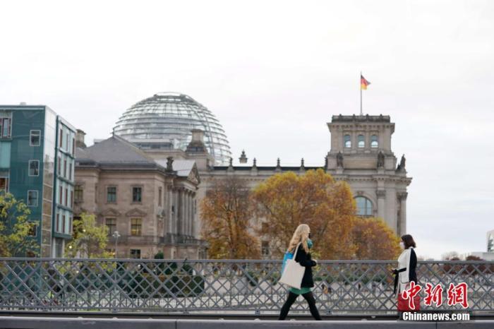 图为16日下午,两名戴口罩的女士从德国国会大厦旁的桥上经过。 /p中新社记者 彭大伟 摄
