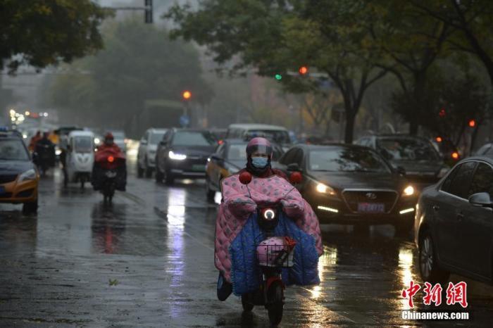 资料图:市民冒雨出行。 中新社记者 田雨昊 摄