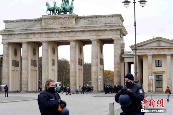 11月18日,德国联邦议院通过了第三版传染病防治法。新法将允许德国政府在新冠疫情期间采取包括入境人员数字登记健康情况、实施快速抗原检测、壮大公共卫生部门等措施。德国卫生部长施潘当天表示,此次修法为德国联邦政府和各州采取必要的防疫措施提供了法律授权。图为当天下午,柏林市在勃兰登堡门部署大批警力,避免反对修法的示威者冲入正在进行表决的国会大厦。 中新社记者 彭大伟 摄