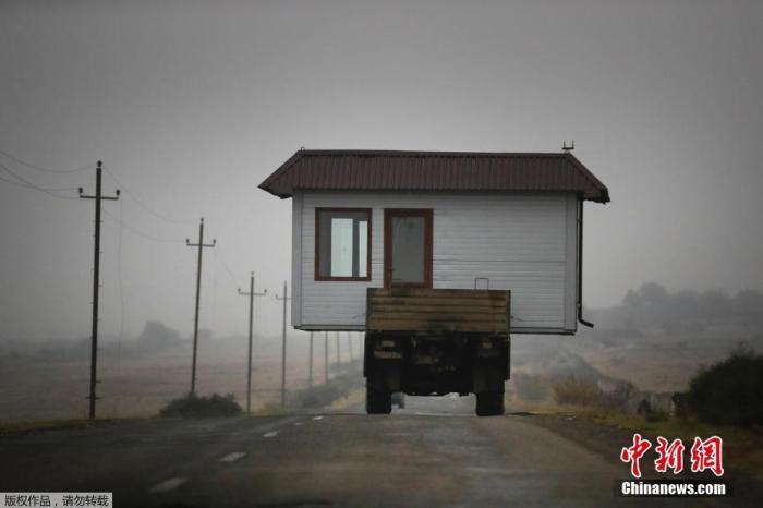 资料图:当地时间11月18日,纳卡地区的一户人家在搬家时将房子放在卡车上带走。据报道,俄罗斯、阿塞拜疆、亚美尼亚三方签署纳卡地区停火协议。目前,俄罗斯已派遣维和部队前往纳卡地区,还将与土耳其成立联合中心,负责对纳卡地区停火声明执行情况进行技术性监督。
