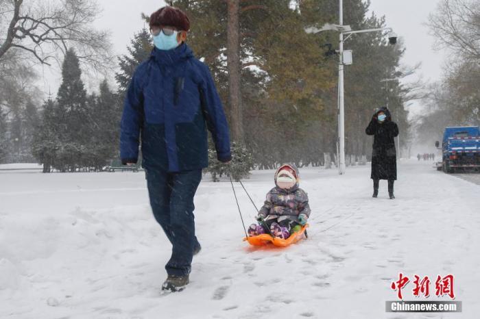 11月19日,黑龙江省哈尔滨市迎来大暴雪天气,虽给当地市民交通出行带来不便,但也营造了银装素裹的冬季美景。图为一名孩童雪中坐爬犁。 /p中新社记者 吕品 摄
