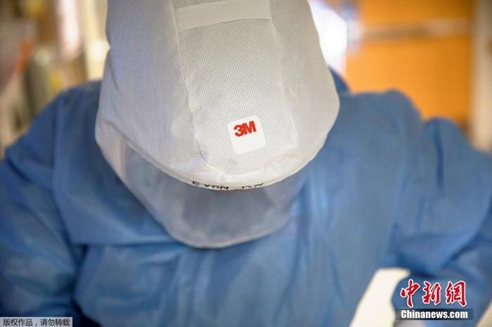資料圖:當地時間2020年11月18日,美國威斯康辛州麥迪遜華盛頓大學衛生大學醫院,醫護人員在進入新冠肺炎患者病房前,佩戴電動空氣凈化呼吸器。