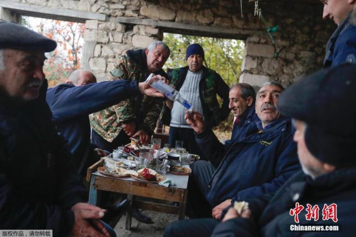 当地时间11月18日,纳卡地区的一个村庄里,当地的亚美尼亚人正在进行最后一次晚餐,晚饭过后他们将搬离这个村庄。