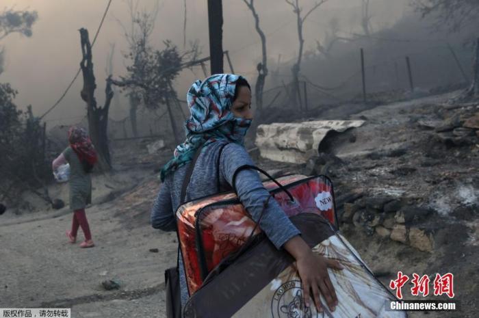 9月9日,希腊莱斯博斯岛的莫里亚难民营发生大火后,一位移民带着自己的物品离开难民营。Elias Marcou