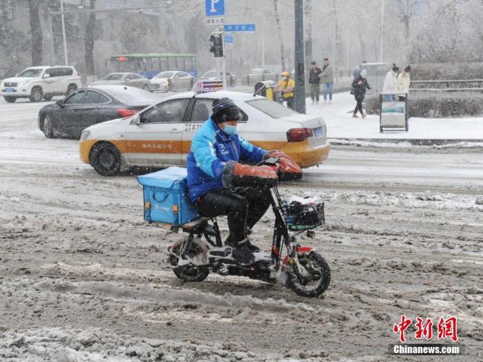 资料图:外卖小哥冒雪送餐。 中新社记者 刘栋 摄