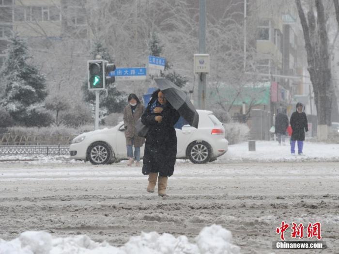 11月19日,吉林长春,市民冒雪出行。当日,吉林长春遭遇暴雪天气。 /p中新社记者 刘栋 摄