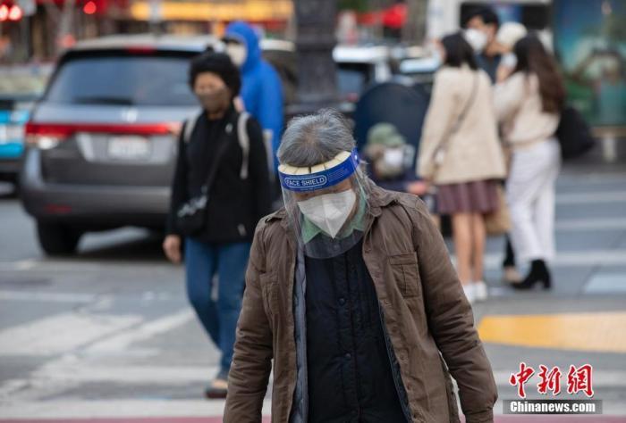 当地时间11月21日,美国加州旧金山市民戴口罩出行。 中新社记者 刘关关 摄