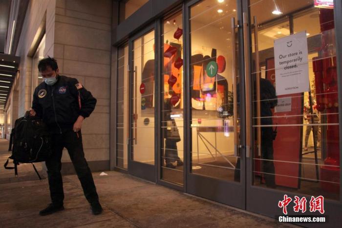 """当地时间11月23日,加拿大多伦多市中心,一位男士在一家关闭的商场门外按照预约取货。由于新冠疫情反弹严重,多伦多和与之相邻的皮尔地区从这一天起划入防疫级别最高的""""灰【se】地区"""",重新实施至少为期28天的封禁。<em></em> 中新社记者 余瑞冬 摄"""