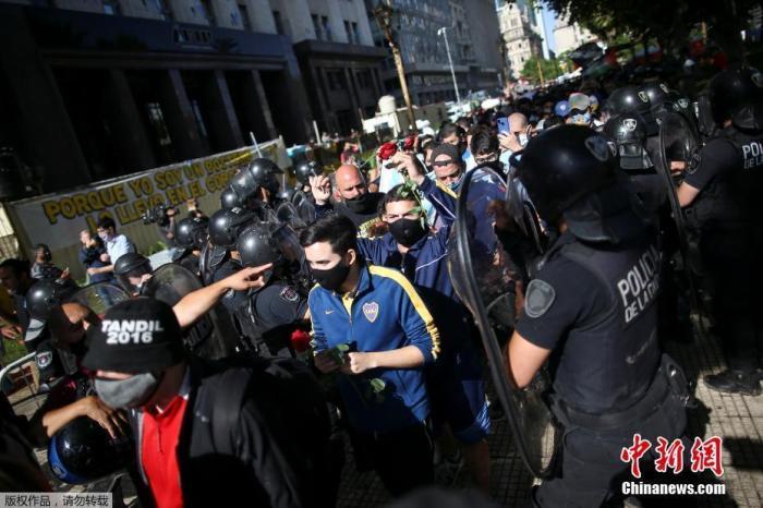 """当地时间11月26日,阿根廷首都布宜诺斯艾利斯,""""球王""""马拉多纳的悼念仪式在总统府玫瑰宫。图为球迷排队等待进入总统府悼念马拉多纳。"""