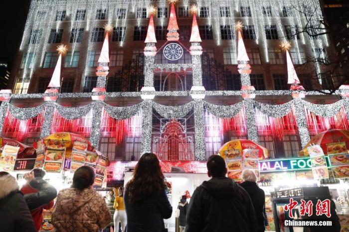 当地时间11月26日,美国传统节日感恩节,纽约第五大道一家商场布置节日灯光秀吸引民众驻足观看。 中新社记者 廖攀 摄