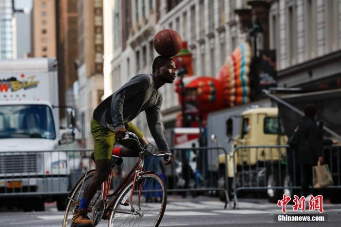 当地时间11月26日,美国传统节日感恩节,纽约梅西百货外一名青年表演骑车顶球庆祝节日。 中新社记者 廖攀 摄