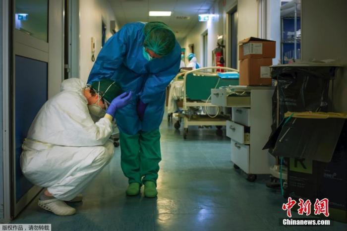 資料圖:當地時間3月13日,位于意大利倫巴第米蘭東南部的克雷莫納醫院,一名戴著防護面具的護士正在安慰另一名換班的護士。Paolo MIRANDA 攝