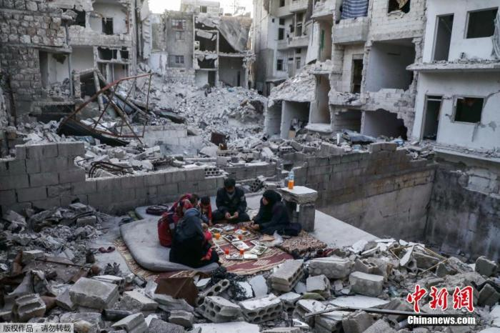 资料图:叙利亚民众在废墟上吃饭。AAREF WATAD 摄