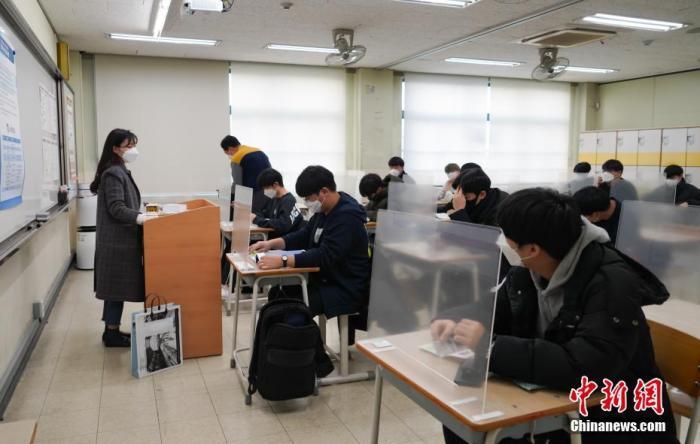 资料图:当地时间2020年12月3日,延迟近一个月的韩国高考举行。据韩国教育部消息,今年考生约49.34万人,创历史最低纪录。图为在首尔某考点内,考桌上设有隔板。 中新社发 首尔市教育厅 供图