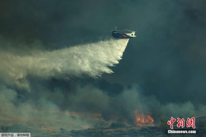 当地时间12月3日,美国加利福尼亚州橙县附近山火蔓延。图为飞机赶赴火场洒水救援。