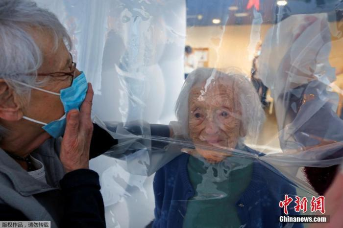 当地时间12月4日,法国热蒙一家养老院内,Marie-Paule和Marie-Josephe隔着塑料帘与97岁的母亲团聚。